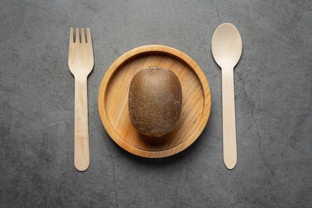Kiwi fresco colocado em prato redondo de madeira