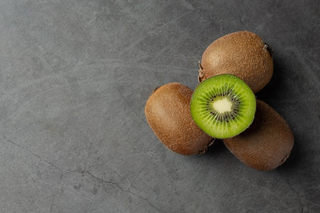 Kiwi fresco, cortado ao meio, colocado no chão escuro
