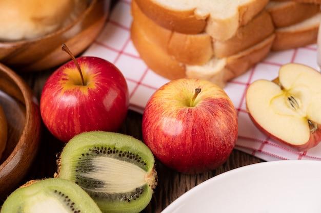Kiwi, maçãs e pão na mesa