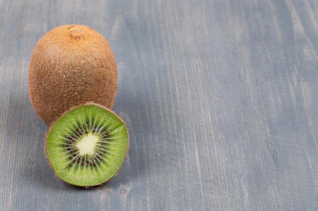 Kiwi maduro e fatia em superfície de madeira