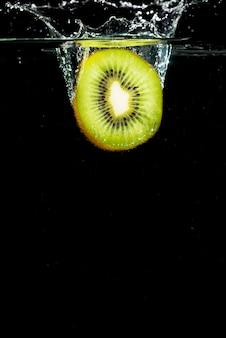 Kiwi verde dividido ao meio que espirra na água