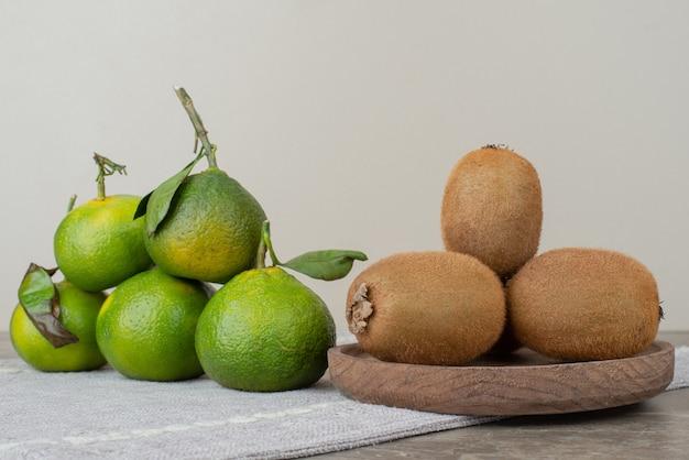 Kiwis e tangerinas frescas na toalha de mesa cinza.