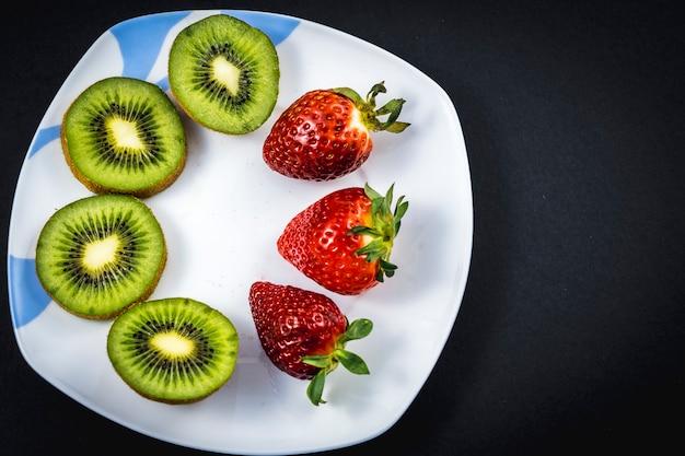 Kiwis fatiados e morangos em um prato branco no preto