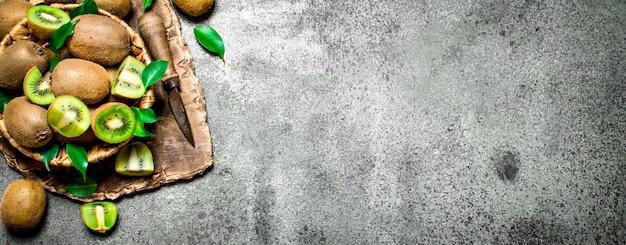 Kiwis frescos na cesta. na mesa rústica.
