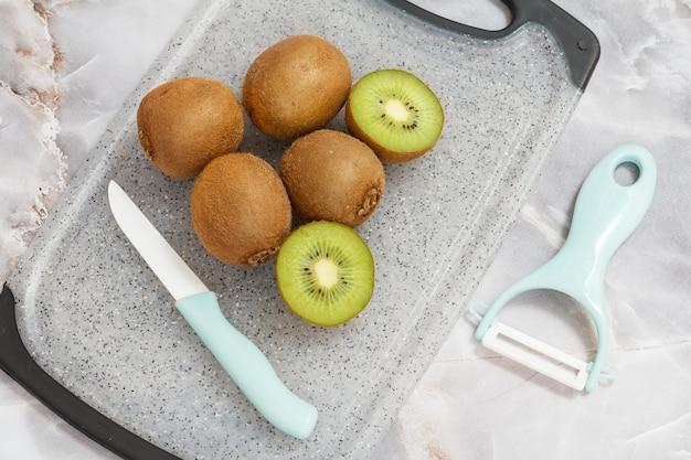 Kiwis inteiros e fatiados e uma faca de cerâmica de cozinha, um limpador em uma tábua de cortar na mesa de pedra da cozinha. comida saudável. vista do topo.