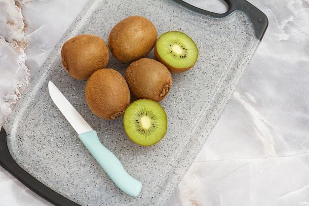 Kiwis inteiros e fatiados e uma faca na mesa da cozinha.