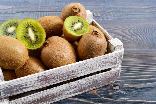 Kiwis maduros frescos em uma caixa de madeira em cima da mesa. fruta tropical. comida saudável.