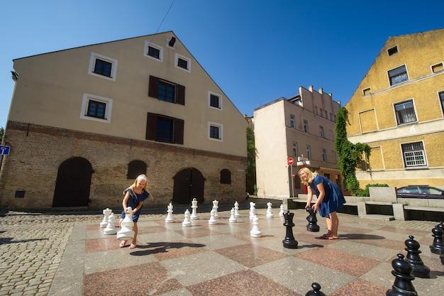 Klaipeda, lituânia uma jovem alegre e uma garotinha seguram peças de xadrez nas mãos