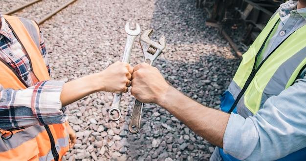 Knuckle bump as mãos do grupo de engenheiros trabalhando no local da garagem de trens e segurando uma velha chave inglesa para conserto