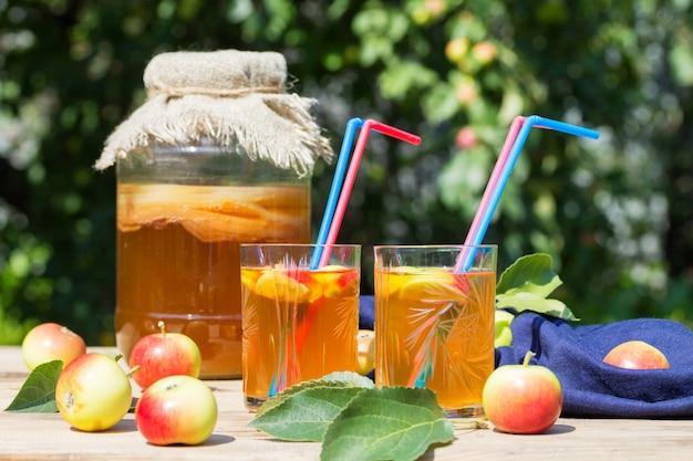 Kombucha beber em uma jarra de vidro e um copo com canudos rosa e azuis, maçãs fermentadas, sobre uma mesa de madeira