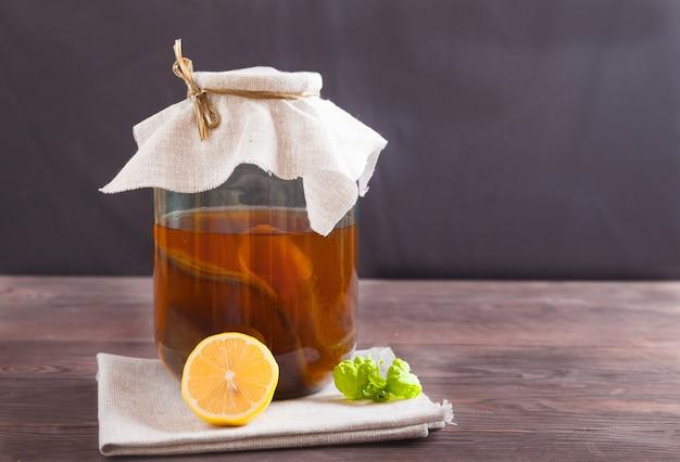 Kombuchá em uma jarra de vidro, limão e uma folha de hortelã em uma mesa de madeira. bebida fermentada. conceito de comida saudável.