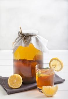 Kombuchá em uma jarra de vidro, um copo com uma bebida e rodelas de limão sobre uma mesa de madeira. bebida fermentada. conceito de comida saudável. vertical.
