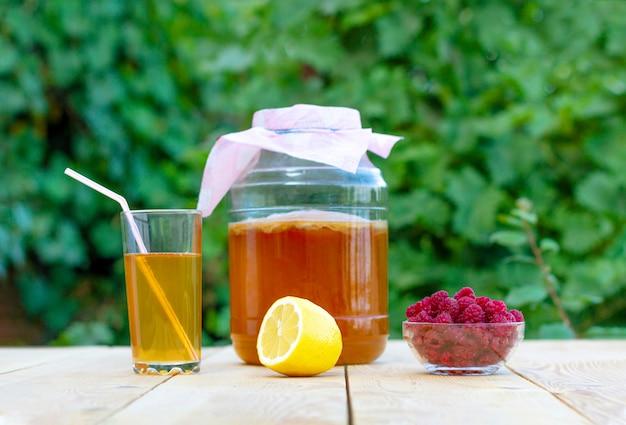 Kombucha em uma jarra sobre uma mesa de madeira clara contra o céu, um copo cheio de kombucha com framboesas.
