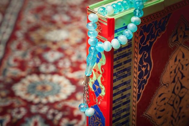 Koran colorido com o rosário na madeira.
