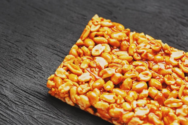 Kozinaki dourado do boleto das barras de energia roasted dos feijões do amendoim. fundo textural preto, vista superior