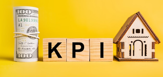 Kpi com modelo em miniatura de casa e dinheiro em um fundo amarelo