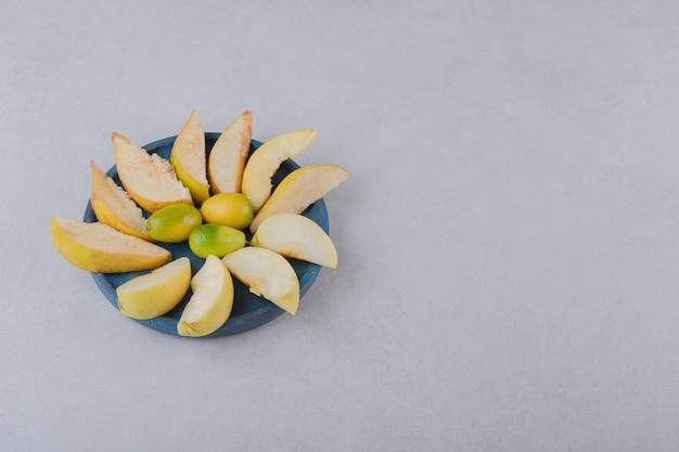 Kumquat e maçã fatiada em uma placa de madeira na mesa de mármore.