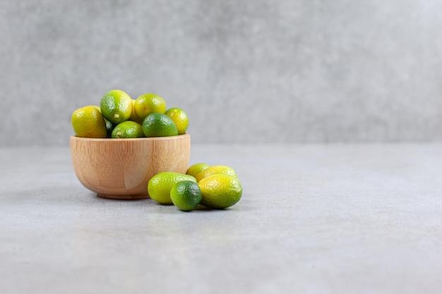 Kumquats dentro e ao lado de uma tigela de madeira com fundo de mármore. foto de alta qualidade
