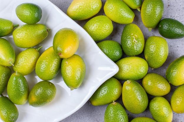 Kumquats e em torno de uma bandeja branca sobre fundo de mármore. foto de alta qualidade