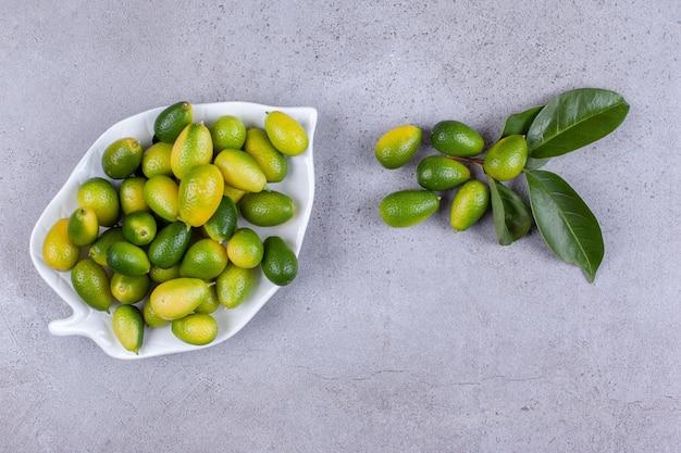 Kumquats em uma bandeja com um punhado ao lado de folhas no fundo de mármore. foto de alta qualidade