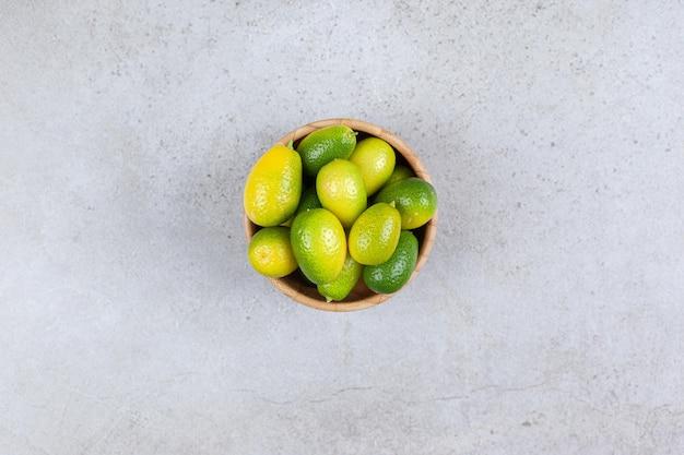 Kumquats em uma tigela de madeira com fundo de mármore. foto de alta qualidade