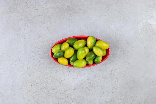 Kumquats em uma tigela oval vermelha sobre fundo de mármore. foto de alta qualidade
