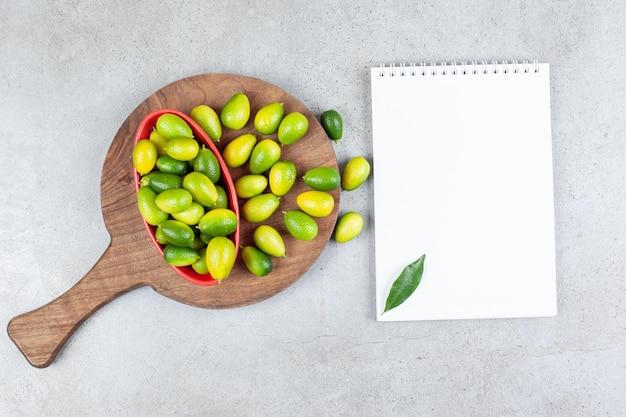 Kumquats empilhados ao lado de uma tigela em uma placa de madeira, ao lado de um caderno adornado com folhas na superfície de mármore