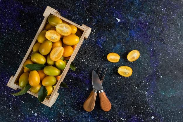 Kumquats orgânicos em caixa de madeira sobre superfície azul