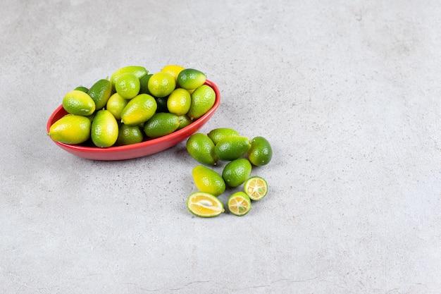 Kumquats verdes empilhados ao lado de uma tigela com algumas fatias abertas na superfície de mármore