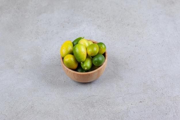 Kumquats verdes empilhados em uma tigela na superfície de mármore
