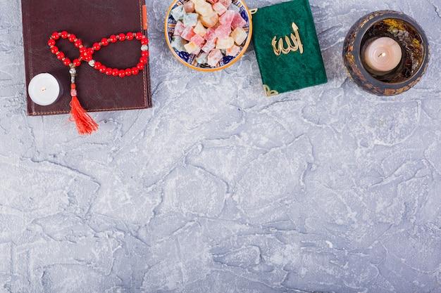 Kuran tradicional; contas de oração; vela acesa com múltiplos rakhat-lukum em pano de fundo concreto