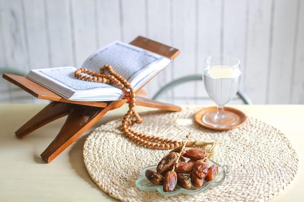 Kurma ou tâmaras frutas com um copo de água, sagrado alcorão e contas de oração na mesa
