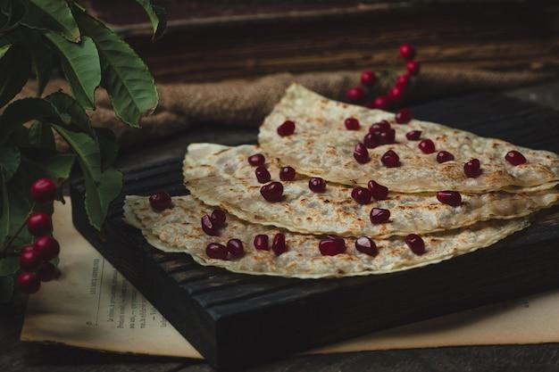 Kutab do azerbaijão com sementes de romã em uma placa preta
