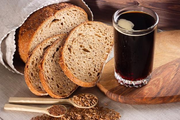 Kvass com pão de centeio e grãos inteiros em colheres de madeira em madeira