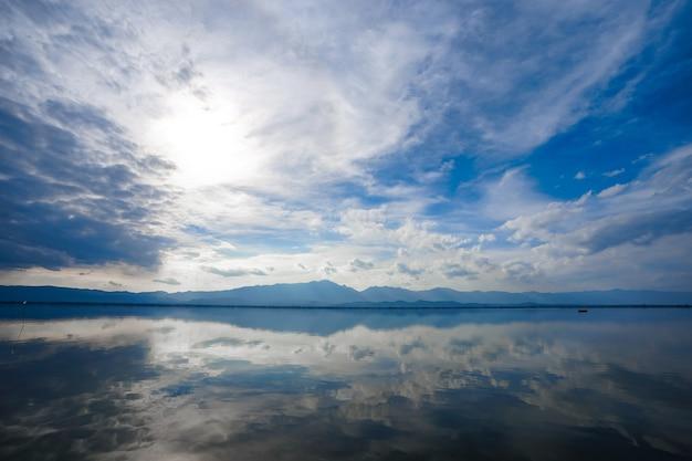 Kwan phayao; um lago na província de phayao, no norte da tailândia. fotografando com a regra dos terços entre rio, nuvem e céu.