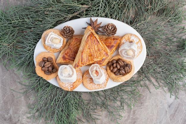 Kyatas, biscoitos, lokums e pinhas em uma travessa sobre mármore.