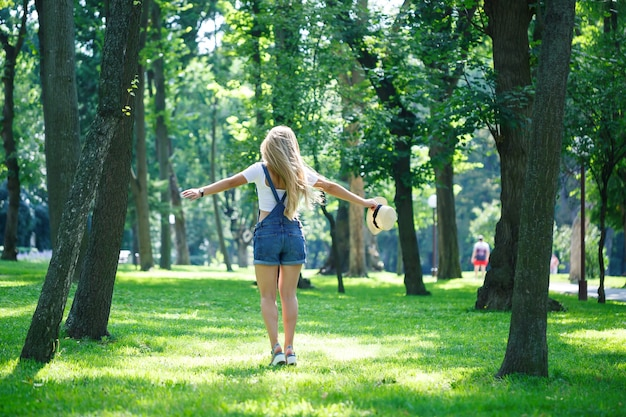 Kyiv, ucrânia - agosto de 2019 linda jovem de macacão jeans e um chapéu leve caminhando no parque