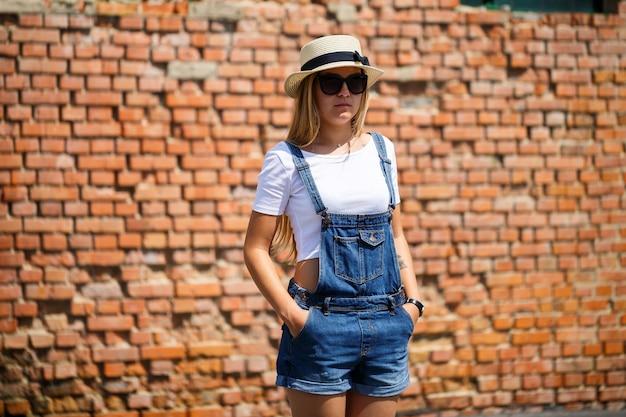 Kyiv, ucrânia - agosto de 2019 menina de macacão jeans, uma camiseta branca e um chapéu claro no fundo de um prédio de tijolos sob o sol forte