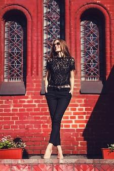 L menina elegante andando e posando em roupas pretas