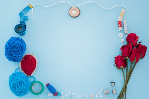 Lã azul; fita métrica; carretel de linha; botão; dedal e rosas sobre fundo azul