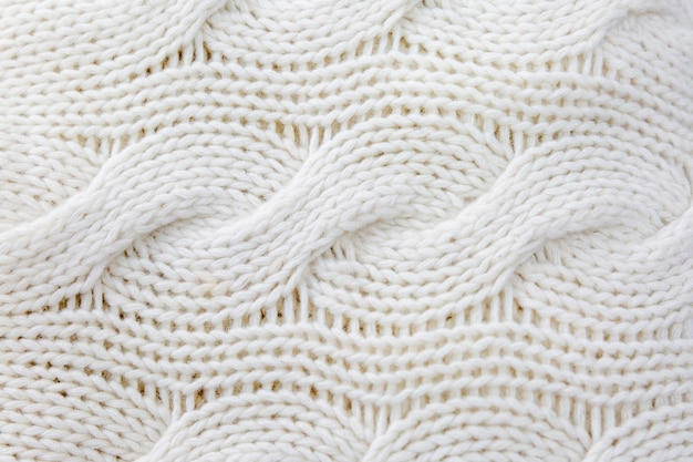 Lã branca tricotada com tranças. fechar-se. fundo. espaço para texto. hobby e habilidade.