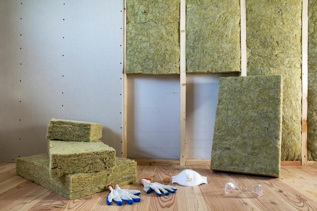 Lã de rocha e material de isolamento de fibra de vidro para barreira contra o frio. ferramentas para trabalhar com lã de vidro: óculos de proteção, óculos e máscara.