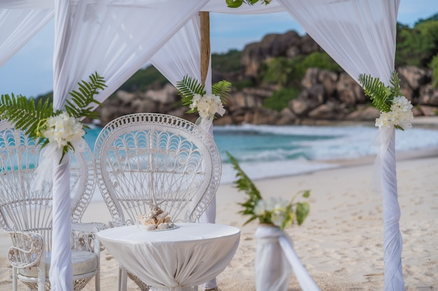 La digue, seychelles. cerimonial de gazebo em arco de casamento decorado com flores brancas em uma praia tropical de areia grande. pedras de granito famosas.