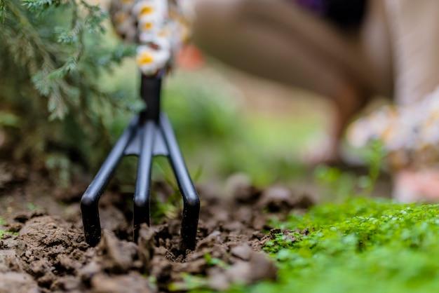 La mano de una mujer excava el suelo y la tierra. primer plano, concepto de jardinería, jardinería. vista a nivel del suelo de la mujer que planta las flores en luz del sol. herramientas de jardinería en el jardín. floreria de mujer trabajando en su invernadero. trabajando en el jardín. guantes de trabajo, herramienta de jardín
