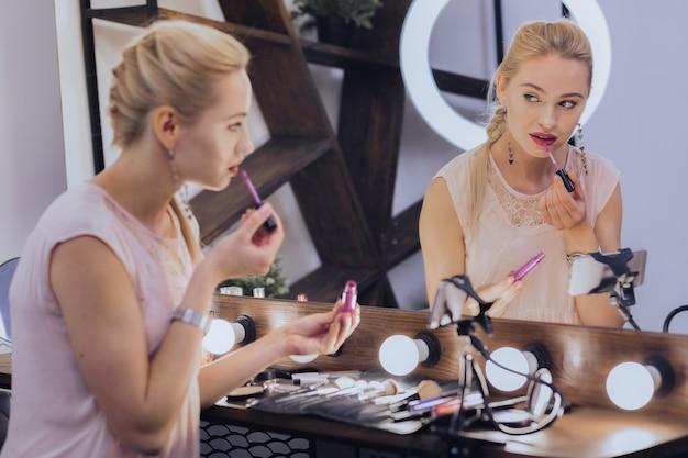Lábios coloridos. bela empresária próspera pintando os lábios antes de sair de casa