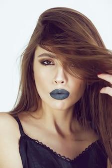Lábios da moda. garota de modelo de beleza com maquiagem preta e longos lacres.