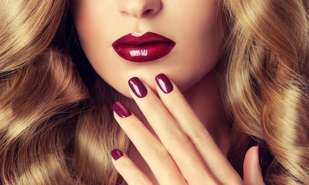 Lábios de mulher perfeitos com forma ideal e coloridos por batom vermelho brilhante e manicure vermelha nas unhas. imagem de noite elegante para mulheres jovens. maquiagem e cosméticos da moda.