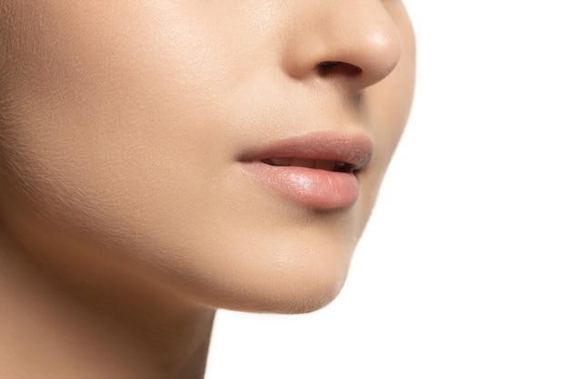 Lábios e bochechas. retrato de jovem modelo feminino isolado na parede branca. linda mulher caucasiana com pele saudável e bem cuidada. estilo e beleza, conceito de cuidados com a pele. fechar-se.