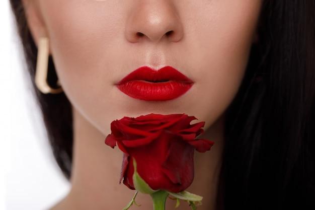 Lábios femininos com maquiagem vermelha brilhante e flor rosa vermelha.