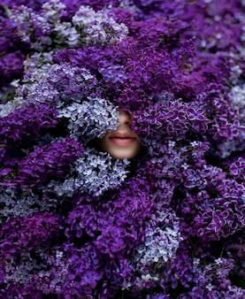 Lábios sensíveis da jovem garota caucasiana cercada com muita violeta lilás, papel de parede, melodia da primavera